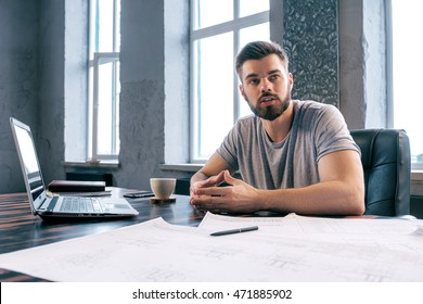 Portrait of bearded and handsome architect discussing project at table with laptop