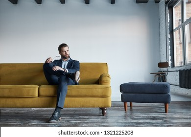 Portrait of bearded and handsome businessman in fashion suit who is resting on sofa in a modern office and looking in window