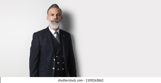 Portrait of bearded handsome businessman wearing trendy suit over empty white background. Copy Paste text space. Wide
