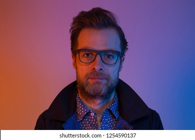 Portrait of bearded handsome forty years old caucasian man in glasses. Colorful light - blue and orange tonal transitions.