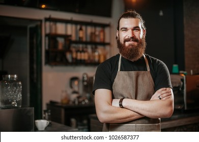 Portrait of bearded happy barista standing at trendy coffee shop, cafe - small business concept. Hipster barista man with beard.