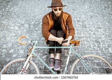 Portrait of a bearded hipster dressed stylishly with brown hat and sweater sitting with retro bicycle on a pavement street