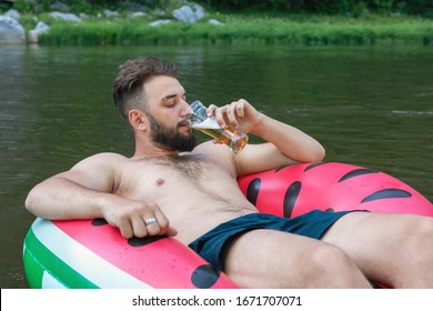 Portrait of bearded hipster guy floating on inflatable circle with glass of beer in his hand. outdoor recreation