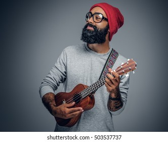 Portrait of a bearded hipster male in red hat playing on ukulele. Isolated on grey background.