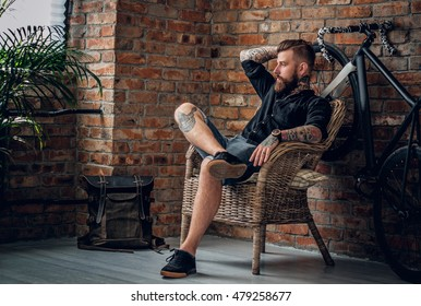 Portrait of a bearded hipster male relaxing in a chair with fix bicycle and the wall from the red brick background.