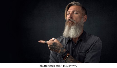 Portrait of a bearded hipster, who is pointing with his finger to the left side, isolated on a black background
