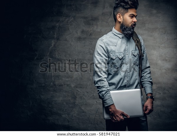Portrait of bearded Indian male holds a laptop.