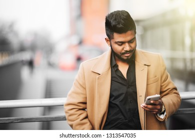 Portrait of bearded indian man in coat use internet networks from phone on the street