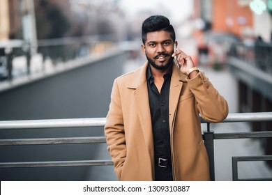 Portrait of bearded indian man talking on the phone on the street