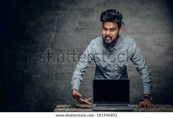 Portrait of bearded Indian near the table with laptop on it.
