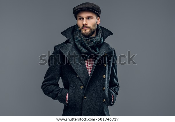 Portrait of bearded male dressed in a grey jacket and a hat isolated on grey background.