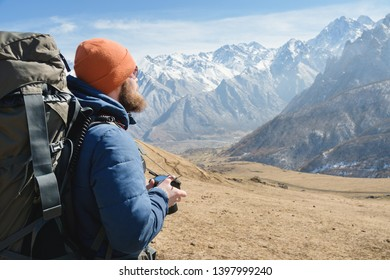 Portrait of a bearded male photographer in sunglasses and a warm jacket with a backpack on his back and a reflex camera in his hands against the background of snow-capped mountains on a sunny day