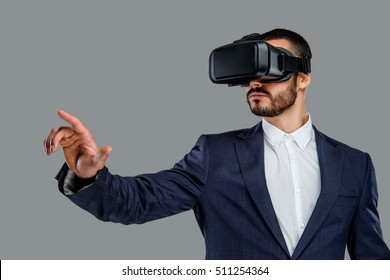 Portrait of bearded male in a suit with virtual reality glasses on his head isolated on grey background.