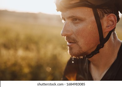 Portrait of bearded man in black helmet feeling tired because of riding bike outdoors. Strong cyclist with drops of sweat on his face  having break during training.