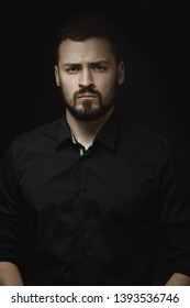 Portrait of a bearded man in a black shirt with an intense look standing indoors in a dark room isolated on a black background. Stylish confident man looking into the camera