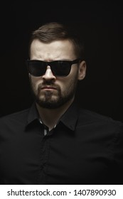 Portrait of a bearded man in a black shirt and sunglasses with an intense look standing indoors in a dark room isolated on a black background. Stylish confident man looking away
