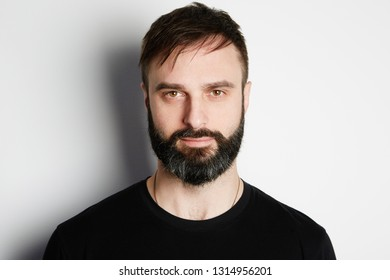 Portrait of bearded man in black tshirt on the empty background.