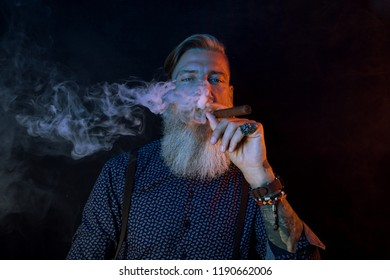 Portrait of a bearded man with a cigar in a blue and red light