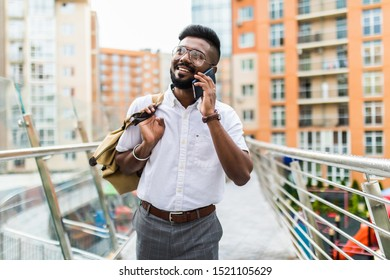 Portrait of bearded man in coat talking on the phone on the street