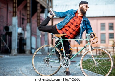 Portrait of a bearded man as a crazy hipster having fun with retro bicycle outdoors on the industrial urban background