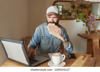 Portrait of bearded man in denim shirt with white and brown cap working on laptop and biting his fresh tasty sandwich and cup of delicious cappuccino in cafe. He is wearing earphones.