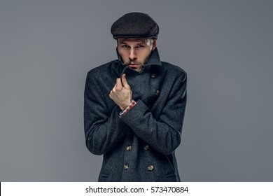 Portrait of a bearded man dressed in a worm jacket and wool cap isolated on grey background.