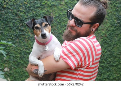 Portrait of a bearded man holds a dog