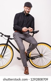 Portrait of bearded man leaning on fixie bicycle play games on the mobile phone over white background
