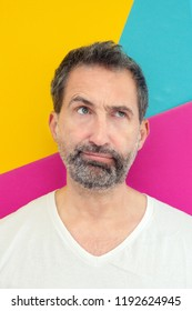 portrait of bearded man looking annoyed with colorful background