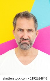 portrait of bearded man looking annoyed in front of colorful background