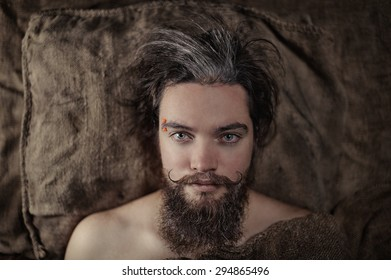 Portrait of a bearded man lying on a burlap bedding