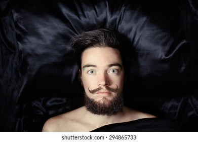Portrait of a bearded man lying on a silk bedding