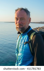 Portrait of bearded man on sea coast. Traveler on the sea coast rests in sunny morning