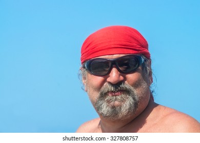 Portrait of a bearded man in a positive red bandana and sunglasses against the blue sky