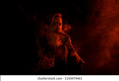 Portrait of a bearded man in red light who is smoking in front of a dark background