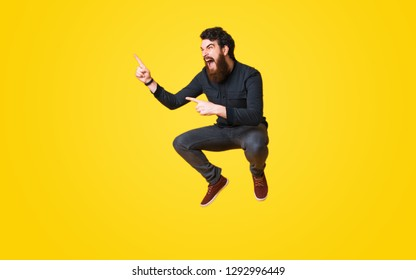 Portrait of bearded man screaming and jumping over yellow background and pointing away