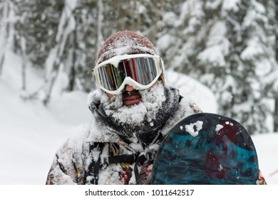 Portrait bearded man ski goggles holding snowboard in the mountains.