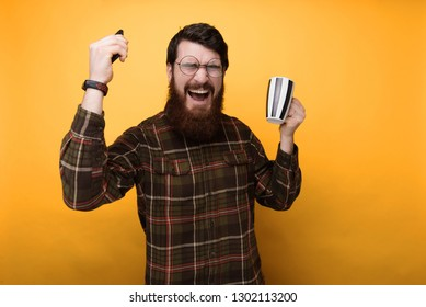 Portrait of bearded man smiling at the friends joke while drinking coffee over yellow background