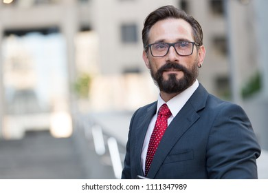 Portrait of bearded man in suit on background of building. Handsome businessman outdoor. Male business person stands on street and looking away. Businessman dressed in formal clothes and glasses.