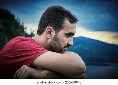 Portrait of a bearded man, wearing a red shirt and hands resting on a railing between the mountains.