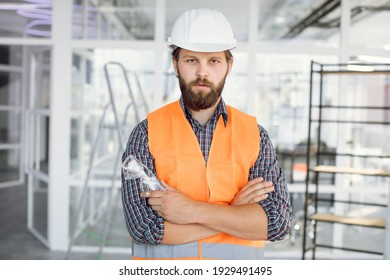Portrait of bearded man wearing uniform and white hardhat at work. Confident contractor standing with crossed arms on building object.