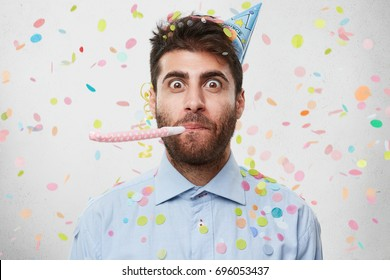 Portrait of bearded man who is celebrating his birthday party, wearing light blue shirt and party cap on head, whistling in party horn, making fun, isolated over white background with colorful papers