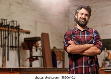 Portrait of a bearded man who owns a small carpentry business, standing in his workshop with with arms folded and showing strong forearms, smiling confidently at the camera