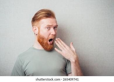 portrait of a bearded man yawns