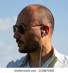 portrait of a bearded mature man wearing sunglasses with headphones, close-up. Age 40 years.