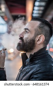 A portrait of a bearded, middle aged, caucasian man smoking a cigar in the streets of Brooklyn, New York City. Shot during the Spring of 2017.