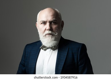 Portrait of a bearded middle-aged man over a gray studio background with copyspace. Serious Senior Man