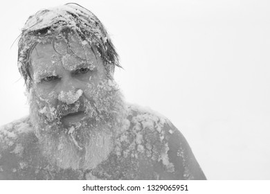 Portrait of a bearded naked man in the snow