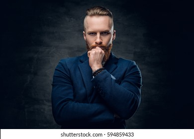 Portrait of bearded redhead hipster male dressed in a blue jacket over grey background.