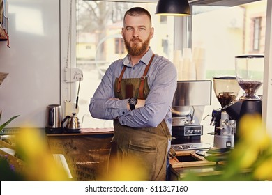 Portrait of bearded redheads seller in a small coffee house.